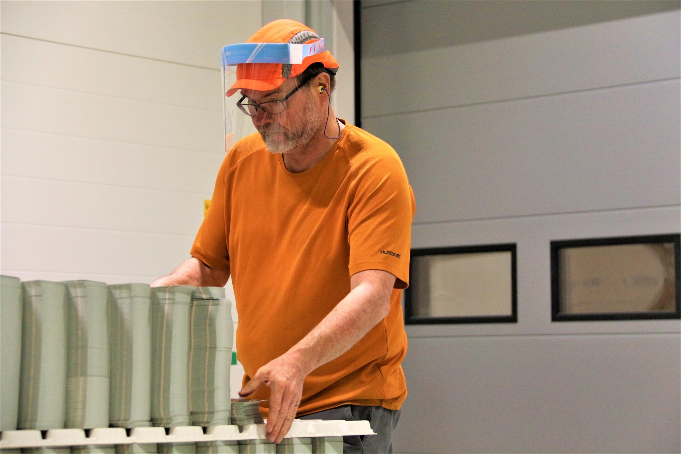 Kartonkikuppiaihiot kohdalleen. Työsuojeluvaltuutettu Jari Oksanen käyttää Huhtamäen tuotantotiloissa kasvosuojana visiiriä.