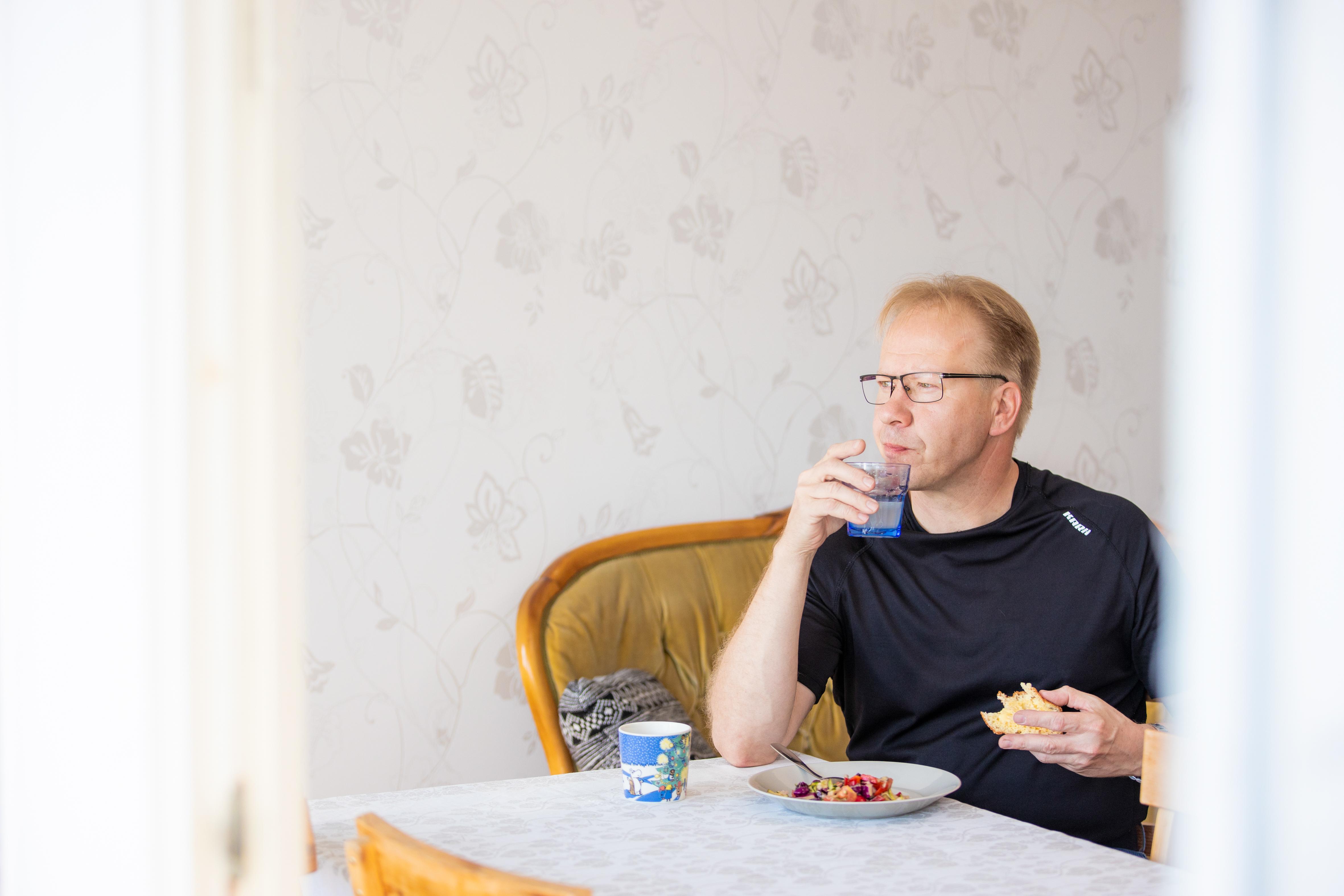 Jari Kettunen amupalalla yövuoron jälkeen. Pöydässä on itse tehtyä leipää ja salaattia.