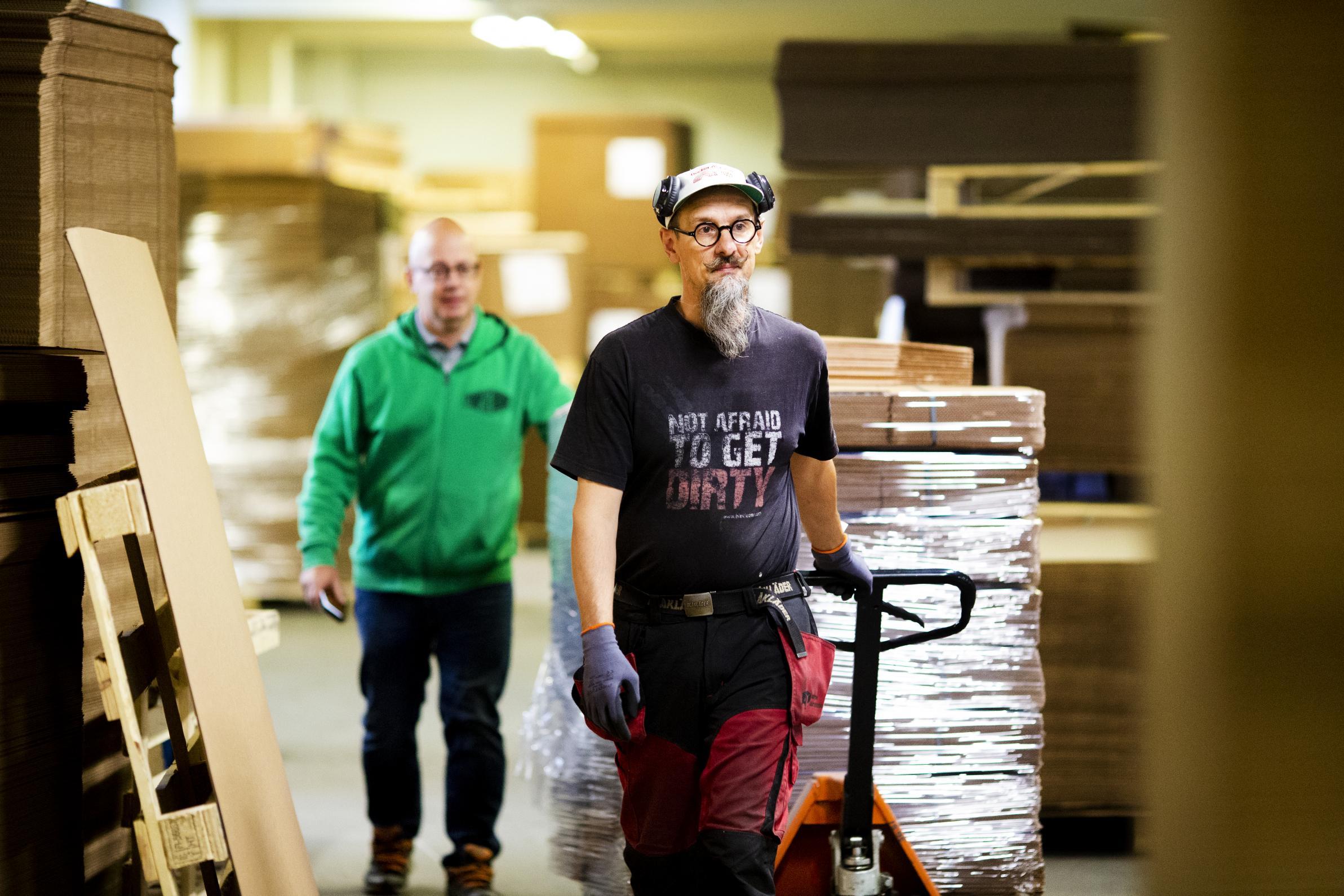 Lavaa siirtävä Markku Keltamäki tuli  laatikkotehtaalle työharjoittelun kautta. Isoveli Mika oli aloittanut työt samalla tehtaalla pari vuotta aiemmin. Perässä kävelee toimitusjohtaja Kari Autio, joka välillä tuuraa tuotannossa.