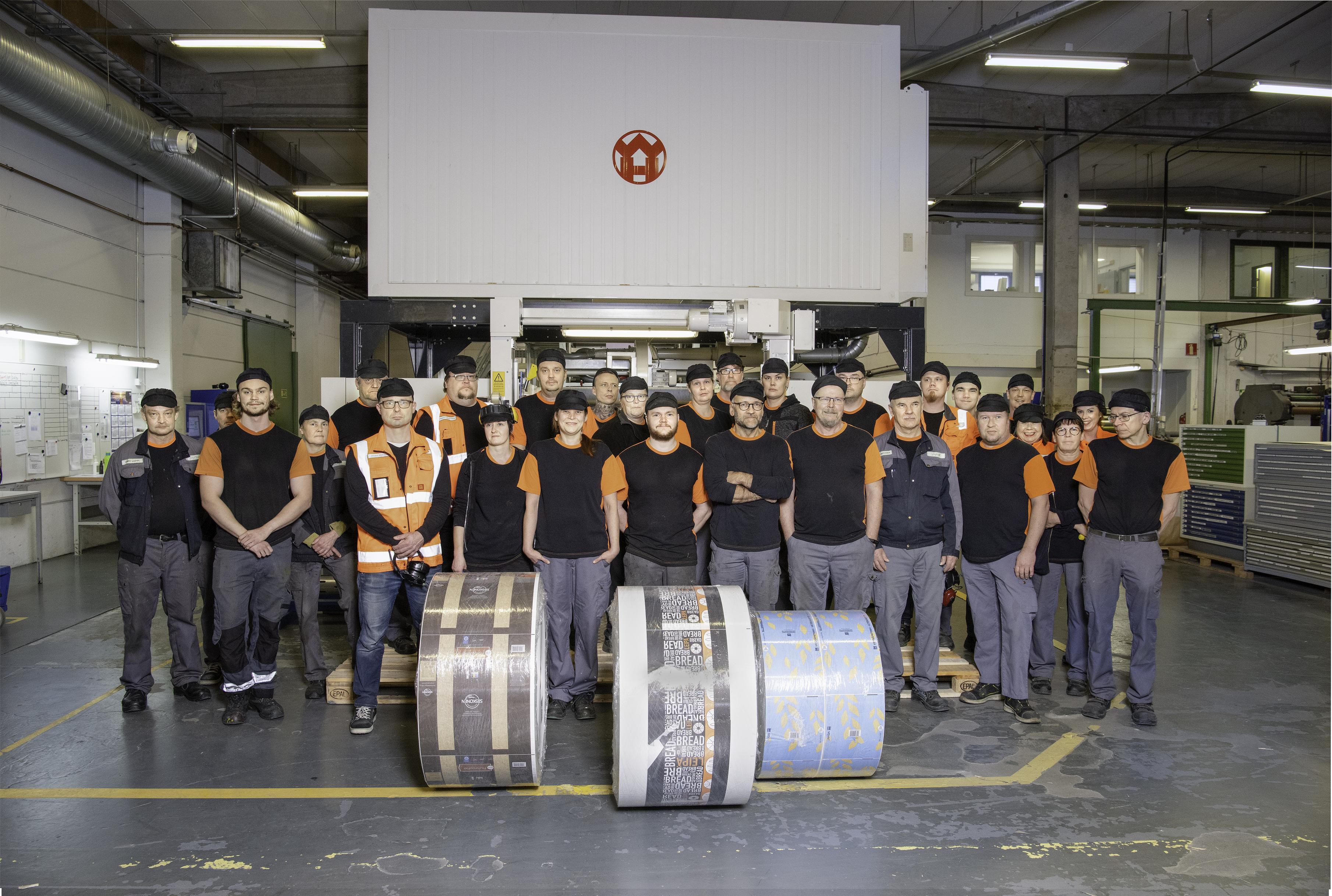 Pyrollpackin Lempäälän tehtaan aamu- ja iltavuoro sekä pari työntekijää toimistonkin puolelta asettuivat uuden paperikoneen eteen.